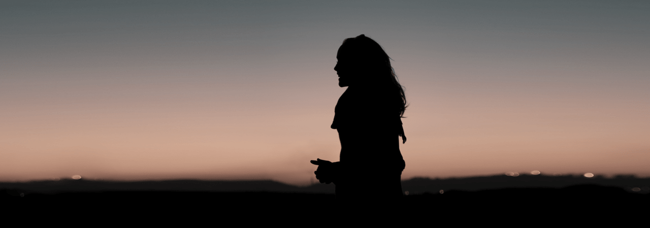 Person with long hair silhouetted by a sunset
