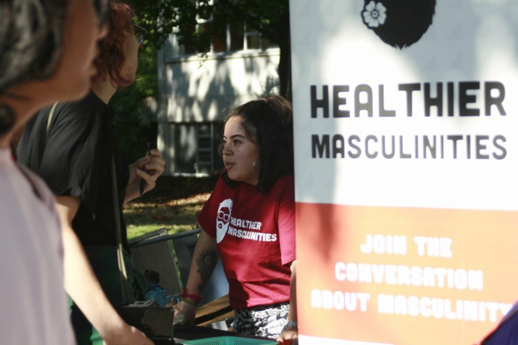 Person at a booth with a sign that reads Healthier Masculinities